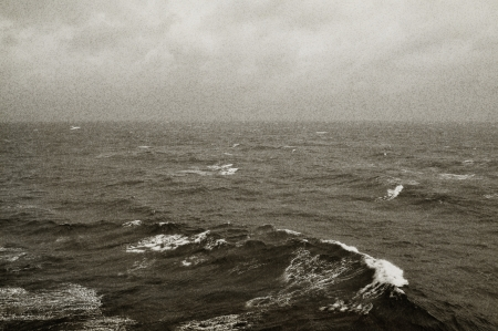 restless: Winter sea waves and cloudy sky horizon. Black and white with grain texture.