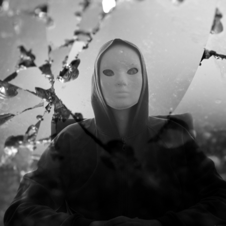 Masked figure reflected through broken glass mirror  Black and white