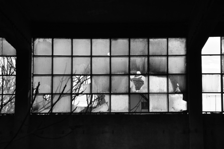 industry moody: Broken windows and concrete wall in abandoned factory  Black and white