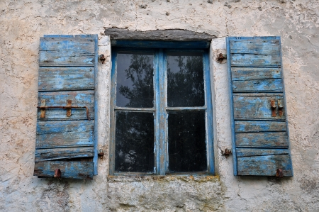 chipped: Wooden window shutter with chipped blue paint and textured wall of old house.