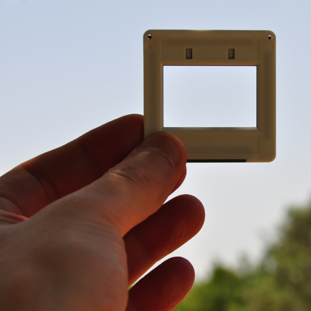 reversal: Hand with blank photographic slide picture frame. Place your own image or text.