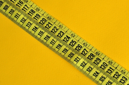 inches: Plastic tape measure inches and centimeters. Abstract numbers yellow background.