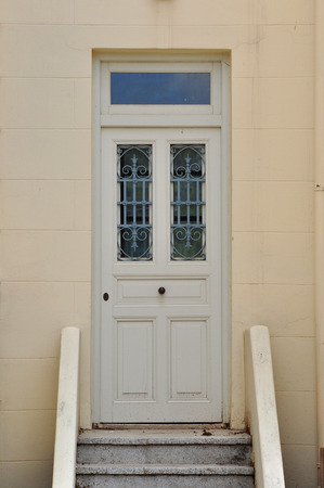 Steps and wooden door with vintage wrought iron pattern. Architectural detail. photo