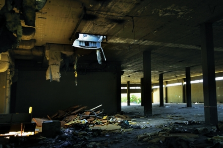 Abandoned factory interior tattered insulation material hanging from the ceiling. Stock Photo - 22304012