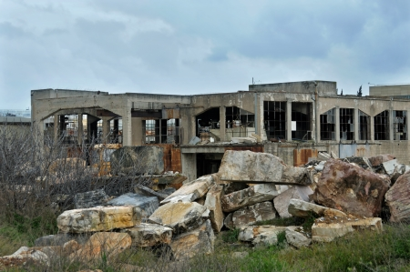 ramshackle: Abandoned marble processing factory exterior and cloudy sky. Industrial decay.