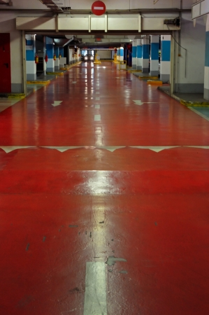 Underground multi-storey car park interior. Red driveway and approaching car.