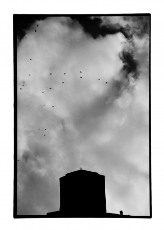 Church silhouette under cloudy sky and flock of flying birds. Old black and white photo darkroom print with dust and scratches, Meteora, Greece circa 1990. photo