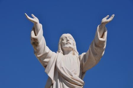 manos levantadas al cielo: Jesucristo con las manos levantadas en señal de bendición bajo el cielo azul. Estatua funeraria de mármol.