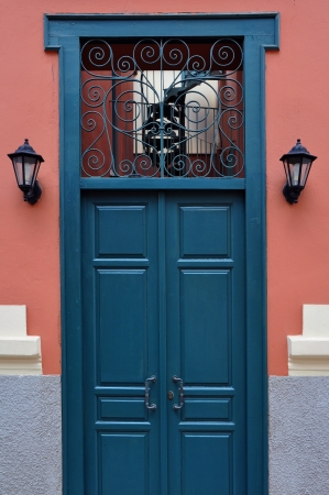 Blue wooden door with antique wrought iron pattern. Architectural detail. photo