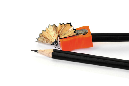 sacapuntas: Sacapuntas y virutas de lápices negros sobre fondo blanco.