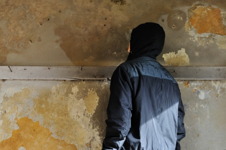 Man looking at textured wall in abandoned house. photo