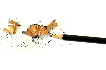 essay: Sharp graphite pencil and shavings on white background.