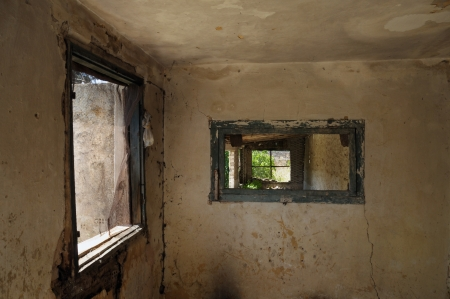 urban decline: Windows and weathered wall in abandoned interior. Stock Photo
