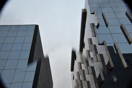 displaced: Modern glass buildings through distortive lens. Abstract city architecture.