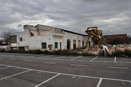 carpark: Abandoned factory exterior and empty parking lot under cloudy winter sky.