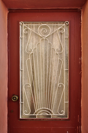 lite: Old wooden door glass lite screen decorated with iron pattern of abstract sun rays and spiral symbols.