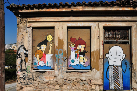 cartoon window: ATHENS, GREECE - APRIL 15, 2014: Colorful graffiti happy cartoon characters on the boarded up windows and door of an abandoned house in Plaka. Editorial