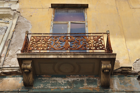 Winged female figure rusty floral pattern and swans on balcony balustrade of abandoned neoclassical house  Athens Greece  photo