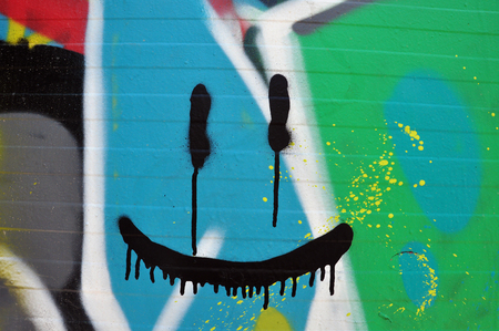 painted face: Abstract smiling face on wall with colorful graffiti and splashed paint. Stock Photo