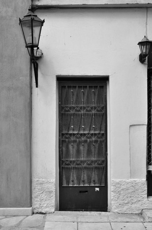 Old door with metal pattern and old fashioned street light. Black and white. photo