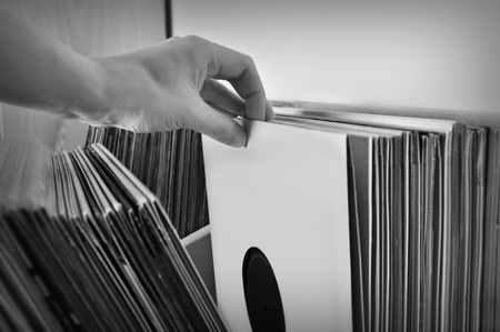Crate digging through vinyl records music collection. Black and white.