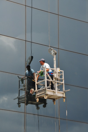 ATHENS, GREECE - JULY 24, 2014: Man cleaning the windows of high rise building glass facade. Working at height dangerous occupation.
