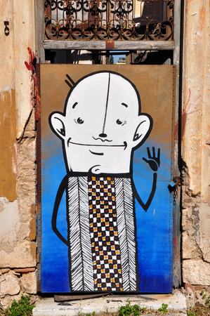 ATHENS, GREECE - APRIL 15, 2014: Funny cartoon character abstract graffiti on the boarded up door of an abandoned house.