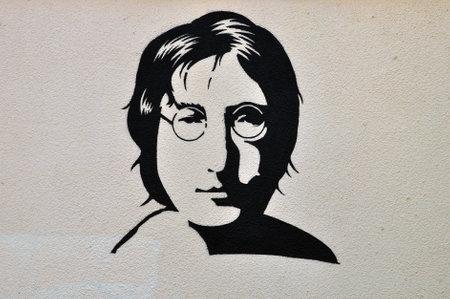 street musician: ATHENS, GREECE - AUGUST 30, 2014: John Lennon portrait stencil graffiti urban art on textured wall.