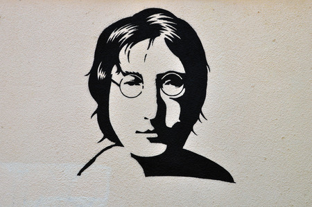ATHENS, GREECE - AUGUST 30, 2014: John Lennon portrait stencil graffiti urban art on textured wall.