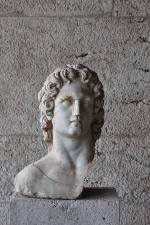 Bust of greek mythology sun god Helios. Broken marble statue of male figure at the ancient agora of Athens, Greece.