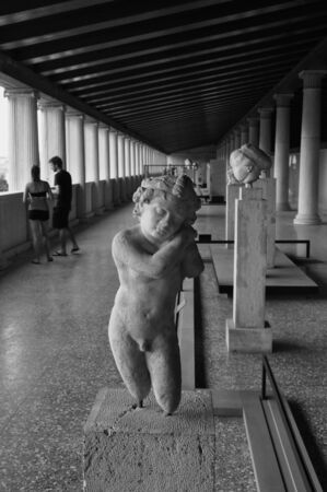 eros: ATHENS, GREECE - SEPTEMBER 2, 2014: Statue of Eros the greek god of love and people visiting stoa of attalos in the ancient agora. Editorial