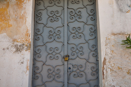 Iron gate with old fashioned metalwork pattern and textured wall background. Abandoned house exterior. photo