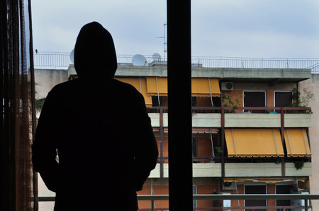 Man looking at city buildings through window. photo