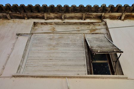 ramshackle: Rusty window shutter and stained white wall. Abandoned house exterior. Stock Photo