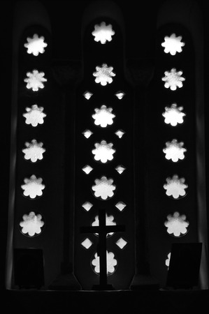 arched: Christian icons and crucifix under arched window in dark church interior. Black and white. Stock Photo