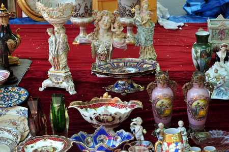 Porcelain vases statuettes and plates antique decorative objects background.