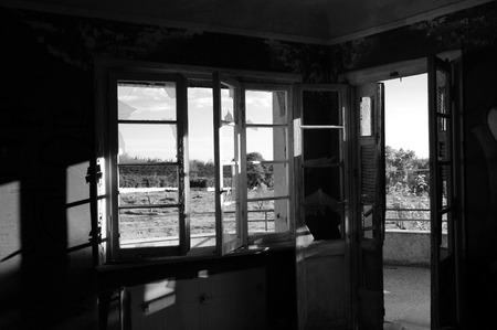 ramshackle: Sunlight shining through broken window and door in abandoned house. Black and white.