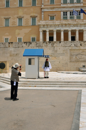 tsolias: ATHENS, GREECE - JUNE 9, 2014: Tourist taking photos of the greek parliament and evzone soldier with traditional uniform guarding the tomb of the unknown soldier. Editorial