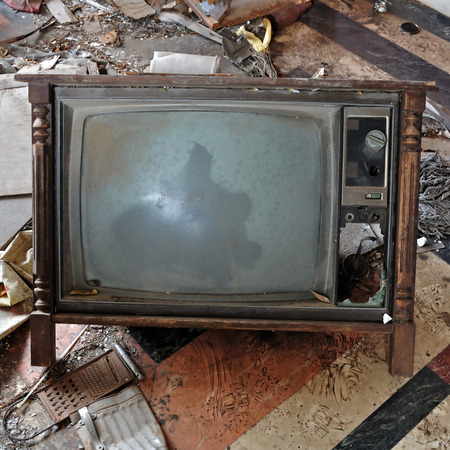 broken house: Vintage tv set with wooden frame. Broken television on the dirty floor of an abandoned house.