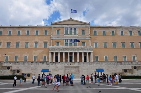 ATHENS, GREECE - JUNE 9, 2014: People visiting the greek parliament in Syntagma square. Tourists taking photos with the evzone soldiers guarding the tomb of the unknown soldier.