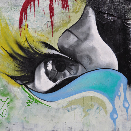 ATHENS, GREECE - DECEMBER 10, 2014: Female eye with big eyelashes and river of tears colorful graffiti on city wall. Urban street art.