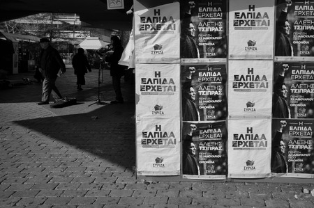 radical: ATHENS, GREECE - JANUARY 28, 2015: Posters of new prime minister of Greece Alexis Tsipras and \Hope is coming\ slogan on campaign kiosk of political party Syriza - Radical Left Coalition. People and street musician black and white. Editorial