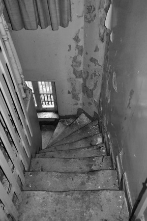 crooked: Crooked wooden staircase and peeling paint wall in abandoned house. Black and white.