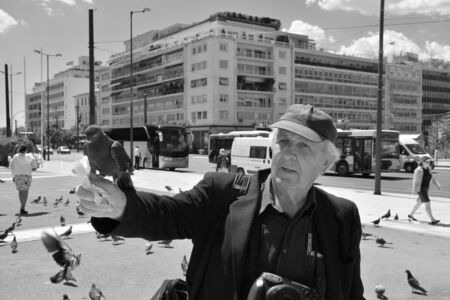 syntagma: ATHENS GREECE  APRIL 22 2015: Man feeding the pigeons and people walking at Syntagma square in downtown Athens Greece.