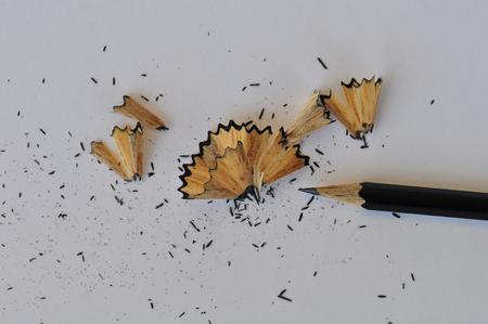 grafit: Naostrzony ołówek grafitowy i wióry na białym papierze. Streszczenie tle.