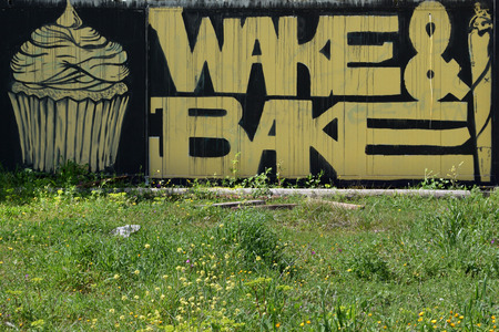 stoned: ATHENS GREECE  APRIL 6 2015: Cupcake and cannabis rolled cigarette graffiti with wake and bake slogan slang for smoking marijuana for breakfast.