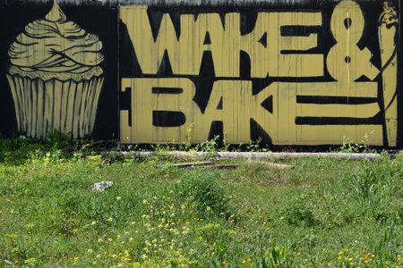 ganja: ATHENS GREECE  APRIL 6 2015: Cupcake and cannabis rolled cigarette graffiti with wake and bake slogan slang for smoking marijuana for breakfast.