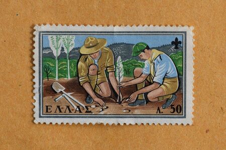 scouts: GREECE  CIRCA 1960: Two boy scouts planting a tree illustration on vintage postage stamp printed by the Hellenic Post.