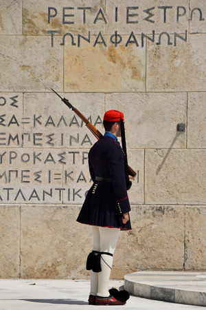 tsolias: ATHENS GREECE  APRIL 22 2015: Evzone soldier with bayonet in traditional uniform tsarouhi shoes and fustanella skirt. Guard at the tomb of the unknown soldier memorial in front of the greek parliament.