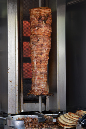 greek food: Pork gyros on vertical broiler rotisserie machine and grilled pita souvlaki bread. Traditional greek fast food.